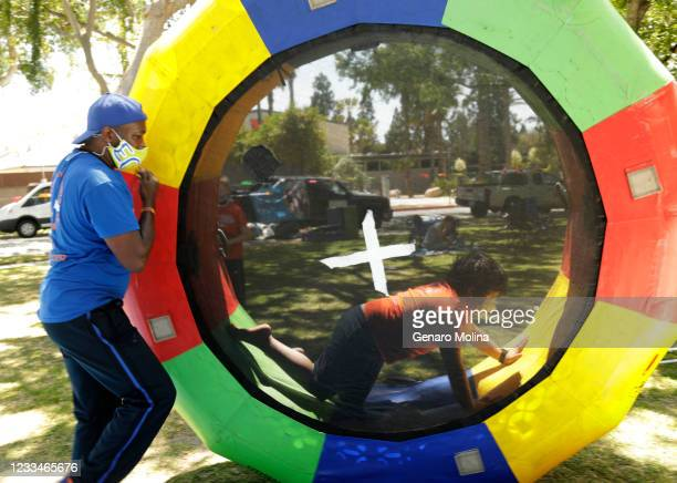 Moyé, co-owner of EC Kids, helps Arya Davani roll an inflatable trampoline during a summer camp at Veterans Memorial Park in Culver City on June 14,...