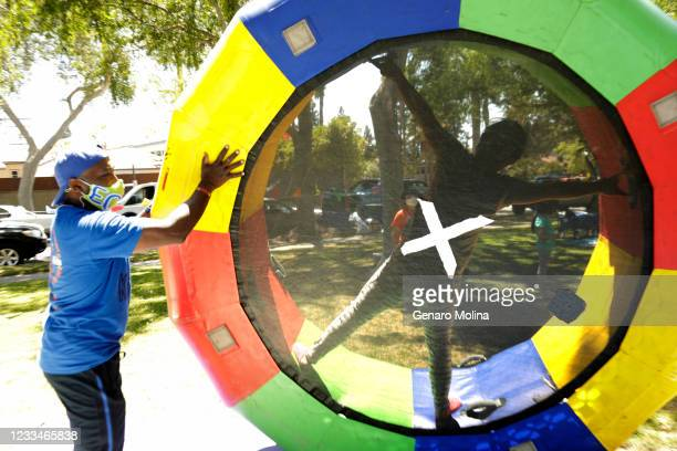 Moyé, co-owner of EC Kids, helps Michelle Kim roll inside an inflatable trampoline during a summer camp at Veterans Memorial Park in Culver City on...