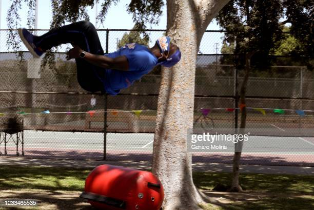 Moyé, co-owner of EC Kids, seems to flip over the warm weather while demonstrating a somersault to children who are participating in a summer camp at...
