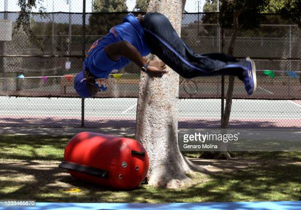 Moyé, co-owner of EC Kids, seems to hang in the air while demonstrating a somersault to children who are participating in a summer camp at Veterans...