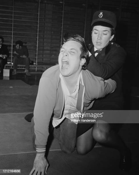 Moya Wood-Heath uses a hair-pulling technique on an attacker played by PC R Andrews, at the Metropolitan Police women's self defence team display at...