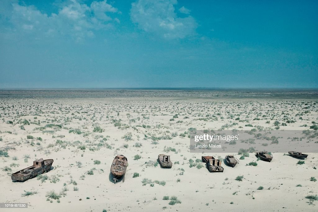 Moynaq / Uzbekistan - MAY 5 2010: abandoned boats rusting away in the sand at the once blooming sea port : Stock Photo