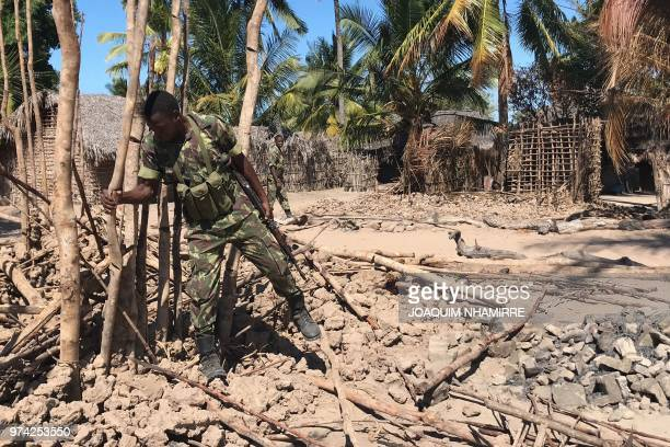 Mozambican Army soldiers bring down a structure torched by attackers to be rebuilt as shelter for people fleeing the recent attacks in Naunde...