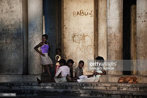 Mozambican children from Beira enjoy the sunset as they sit on the main entrance of the Grand hotel Beira on November 2 2010 in Beira Mozambique The...