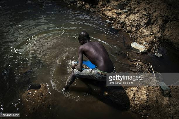 Mozambican gold panners search for gold along the Nhaduwe River outside the Gorongosa Park on May 25 2016 in Gorongosa / AFP / JOHN WESSELS