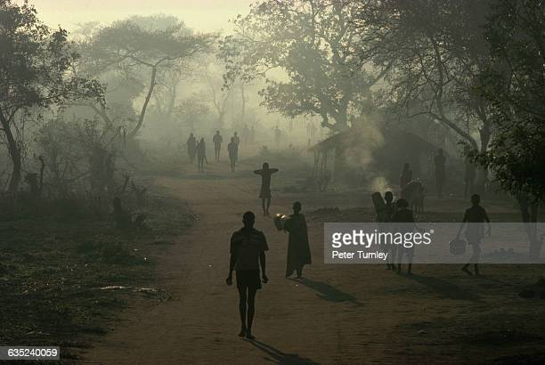 Mozambican refugees walk through smoke and haze along a road in a refugee camp in Malawi