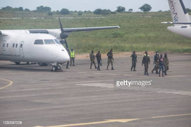 Mozambican soldiers are seen leaving a plane parked on the tarmac of the airport in Pemba on March 31, 2021. - Sporadic clashes broke out in Palma on...