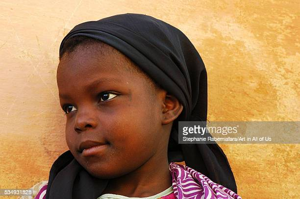 Mozambique Ilha de Mozambique closeup of a girl by wall wearing black headscarf and looking away