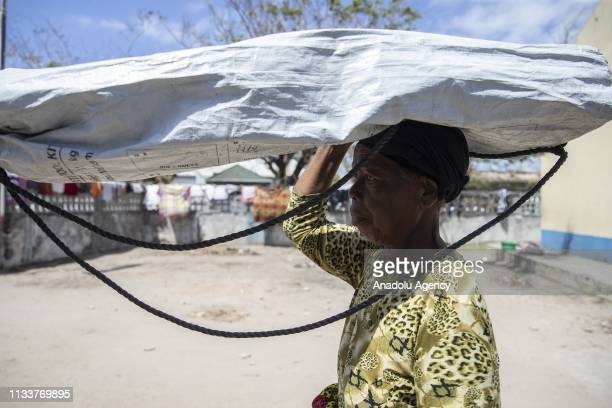Mozambiquean woman carries a bag after taking shelter at Palmeiras 1 school following the Cyclone Idai in Beira Mozambique on March 30 2019 Turkish...