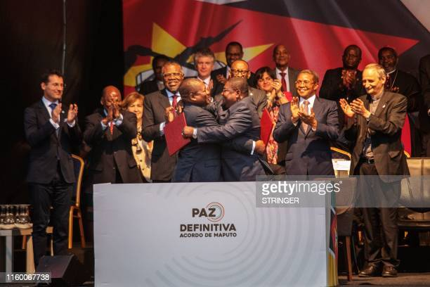 Mozambique's President Filipe Nyusi and RENAMO leader Ossufo Momade hug each other after signing a ceasefire agreement in Maputo, Mozambique, on...