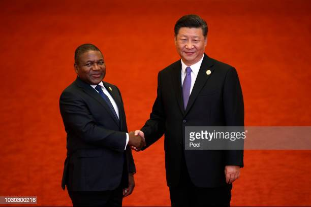 Mozambique's President Filipe Nyusi, left, shakes hands with Chinese President Xi Jinping as they pose for photograph during the Forum on...