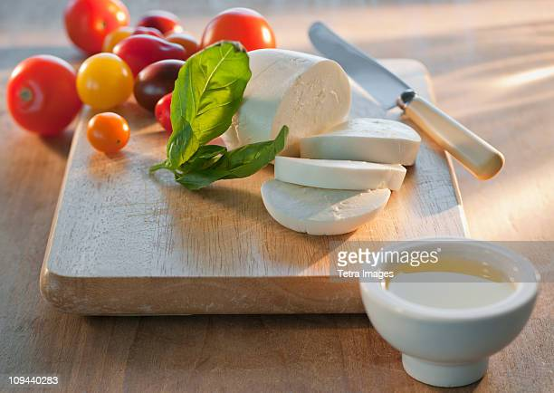 Mozarella and tomatoes on chopping board