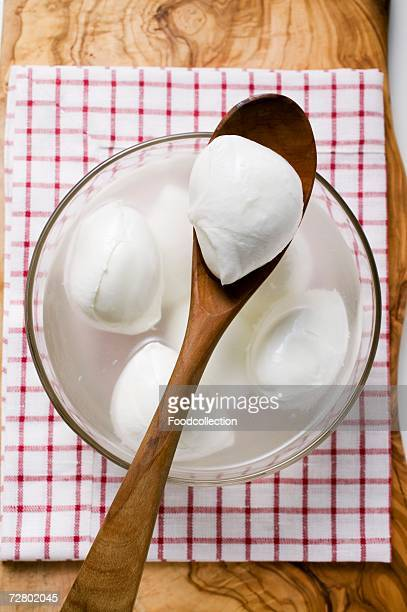 Mozzarella with brine in glass bowl and on wooden spoon