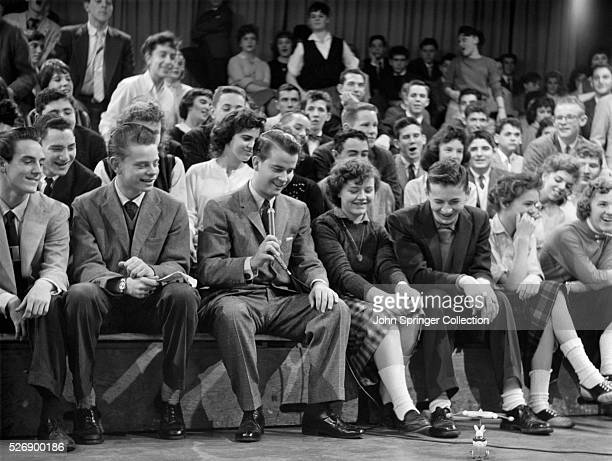mpene from Dick Clark's 'American Bandstand' in which Clark sits in the audience with his teenage audience to watch a toy on the ground before them...