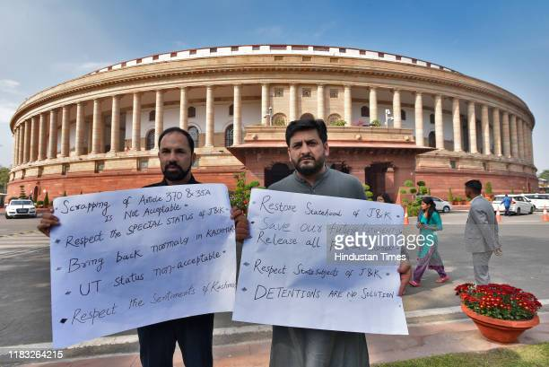 MPs Mir Fayaz and Nazir Ahmed Laway hold placards as they protest against the scrapping of Article 370 and 35A on the first day of the winter session...