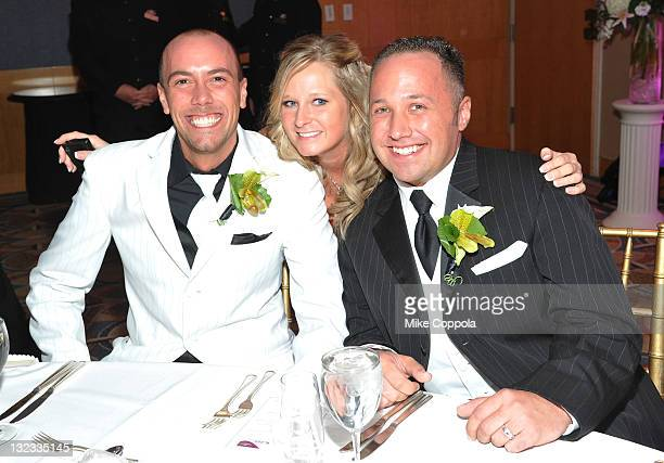 Mr and Mr Bret and Anthony Browning pose with a guest at a wedding for 11 couples at the Crowne Plaza Times Square on November 11 2011 in New York...