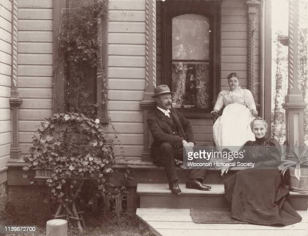 Mr and Mrs Chas Joss and Mrs Van Dyke sit on a residential porch Madison Wisconsin 1899 A planter of ivy is in front of a narrow window on the left...