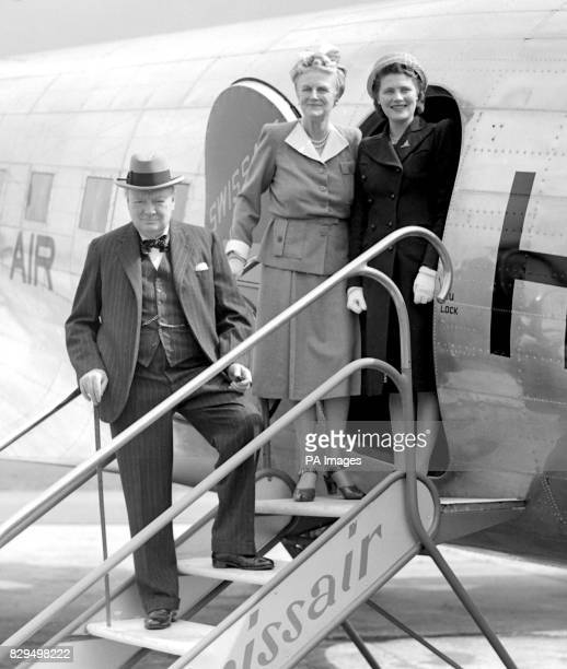 Mr and Mrs Churchill, with Miss Mary Churchill, on the steps of their aircraft at Biggin Hill aerodrome, London, before taking off for Switzerland....