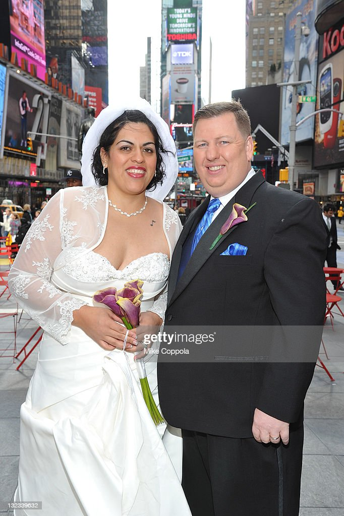 Mr. and Mrs. Dan (R) and Myrna Wilkins pose at a wedding for 11 couples at the Crowne Plaza Times Square on November 11, 2011 in New York City.