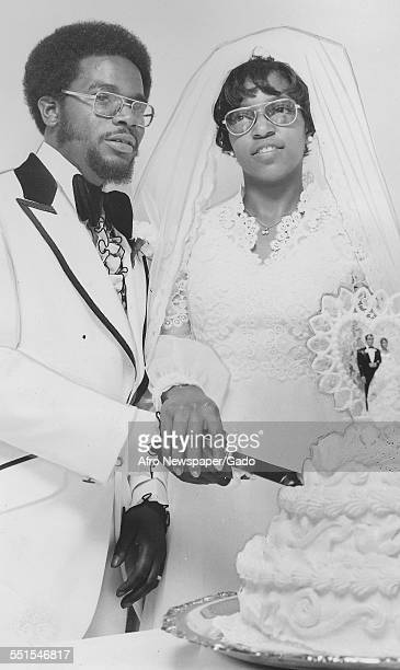 Mr and Mrs John Roscoe Williams a couple at their wedding in formal clothes cutting a large tiered wedding cake May 17 1975