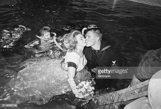 Mr and Mrs Klotz a Navy sailor and his bride kiss above the surface after their underwater scuba diving wedding ceremony
