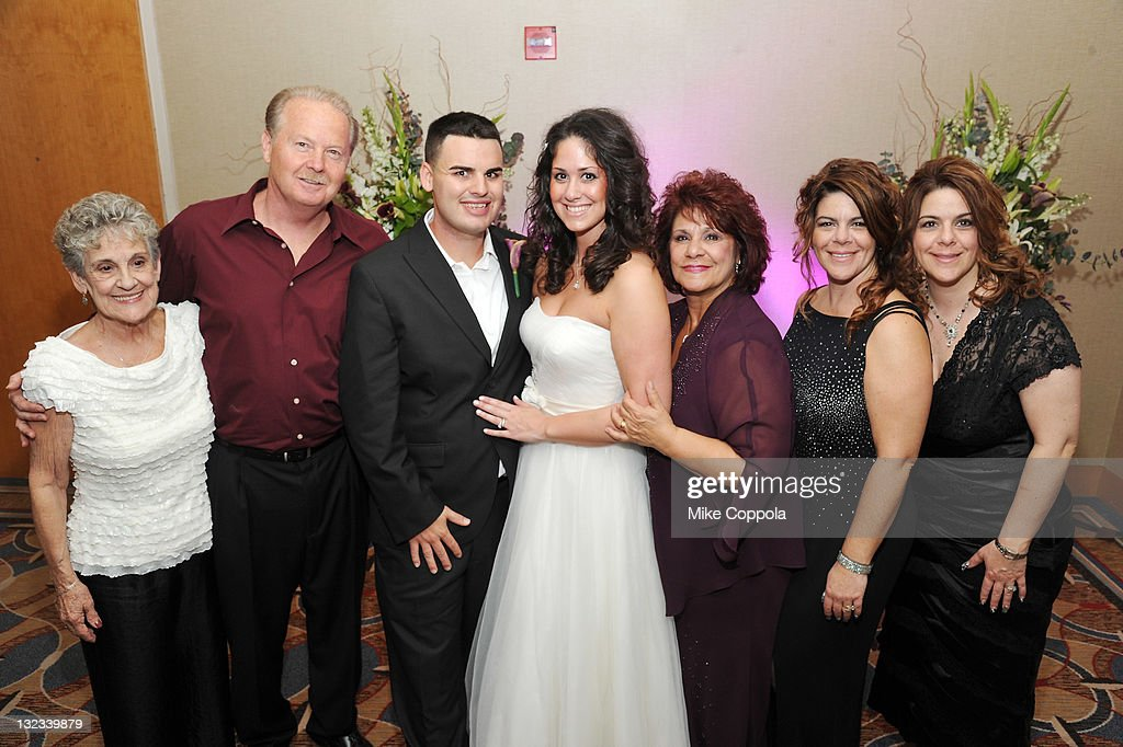 Mr. and Mrs. Kyle Anderson pose with guests at a wedding for 11 couples at the Crowne Plaza Times Square on November 11, 2011 in New York City.