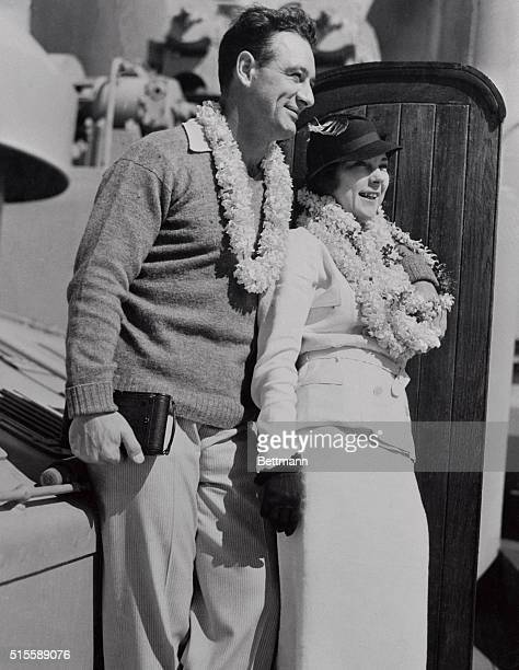Mr and Mrs Lou Gehrig smile their greetings to Hawaii in return for the floral lei with which they were greeted upon their arrival there while en...