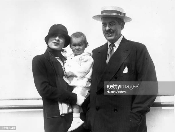 Mr and Mrs Reginald C Vanderbilt standing outdoors posing with their baby daughter Gloria Vanderbilt