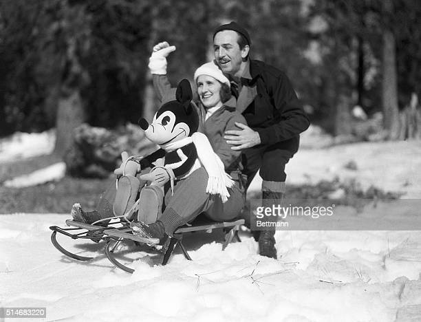Mr and Mrs Walt Disney rest on a sled with a stuffed Mickey Mouse as they greet children to a snow party at the Lake Arrowhead resort area
