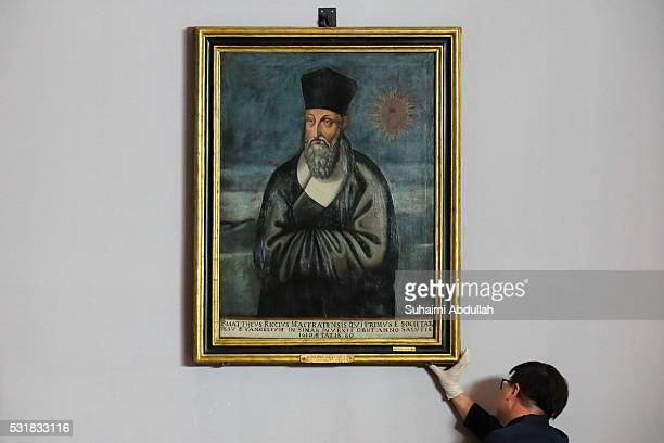 Mr Clement Onn, curator of the exhibition checks on the painting of Matteo Ricci by artist, Emmanuele Pereira after it is installed at the Asian...