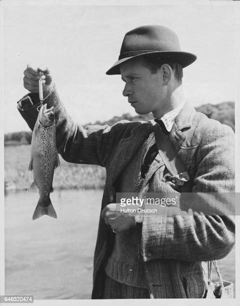 Mr D Wilson who has been fly fishing for trout on the river Itchen examines his 1pound 6ounce catch | Location Near Winchester Hampshire England UK