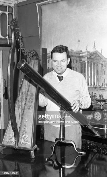 Mr Edward Butler with a victorian brass telescope in his antique shop in Bachelors Walk Dublin