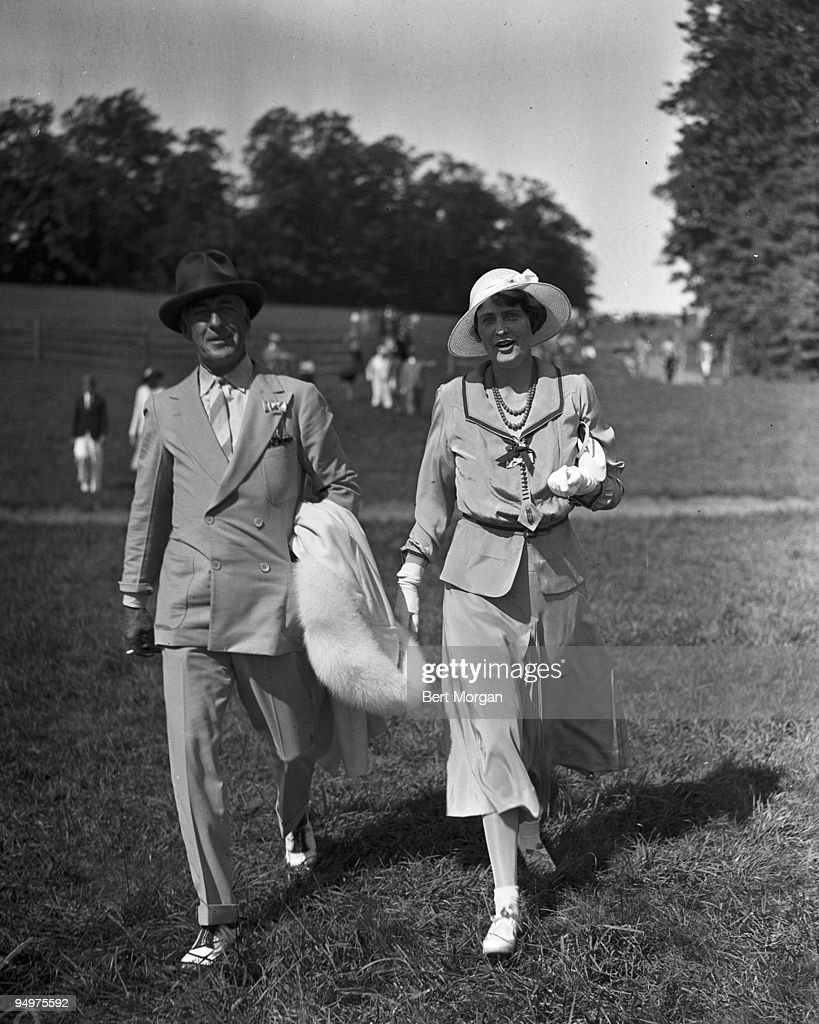 Mr Edward F Hutton, co-founder of the stock brokerage E.F. Hutton & Co, and his second wife General Foods heiress Marjorie Merriweather Post, cross a lawn at the Meadowbrook Cup Races, Old Westbury, Long Island, NY, c1933. They are the parents of actress  : News Photo