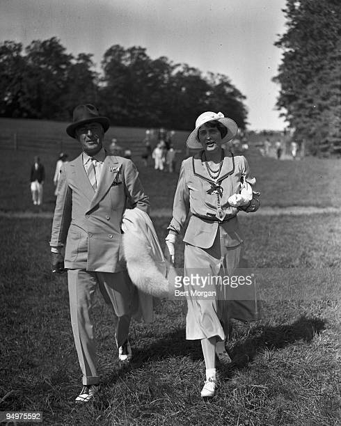 Mr Edward F Hutton cofounder of the stock brokerage EF Hutton Co and his second wife General Foods heiress Marjorie Merriweather Post cross a lawn at...