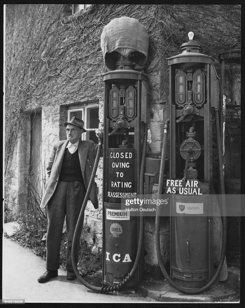 Mr. E.J. Cripps, owner of the Withington village garage, stands beside two petrol pumps which he has been forced to close down as a result of an increase in taxes. | Location: Withington, Gloucestershire, England, UK.
