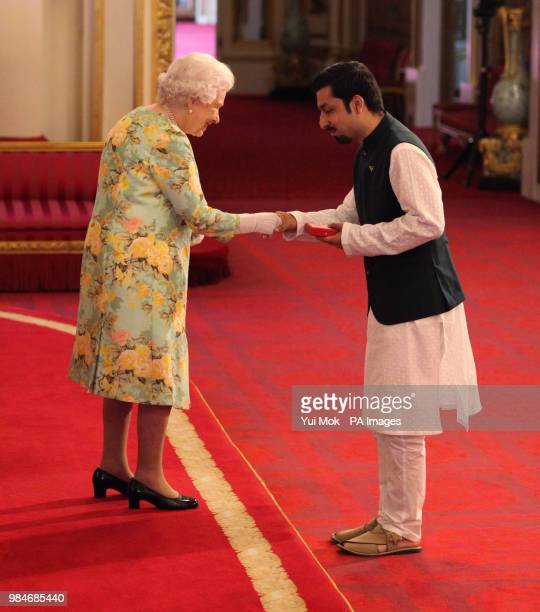 Mr Hassan Mujtaba Zaidi from Pakistan receives his Young Leaders Award from Queen Elizabeth II during a ceremony in the Ballroom at Buckingham Palace
