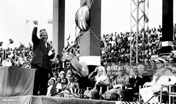 Mr Jomo Kenyatta Prime Minister of Kenya waves his flywhisk to acknowledge the enthusiasm of the crowd after accepting the instruments of Government...