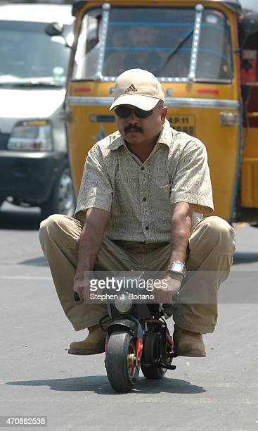 Mr K Sudhakar rides a small motorcycle outside the Sudha Cars Museum He is a Guinness World Record holder for making the Largest Tricycle in the World