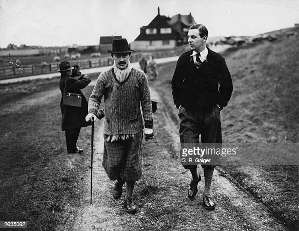 Mr Leonard Crawley and Mr Roger Wethered stroll along a track in Rye where the annual meeting of the Oxford and Cambridge Golfing Society tournament...