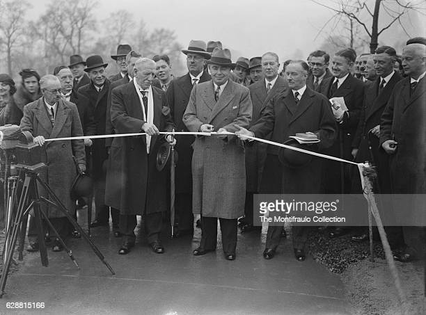 Mr Leslie Hore Belisha the Minister for transport cutting the tape as as he opens the first cyclist track at Western Avenue Greenford as a large...