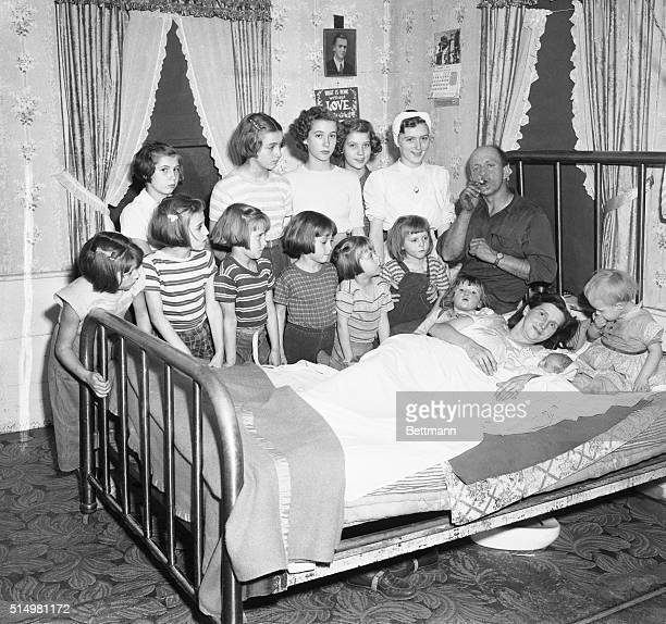 Mr Lloyd Brooks lights a cigar in celebration of his 14th child a boy in an allgirl household Thirteen Brooks daughters gather at the bedside of Mrs...