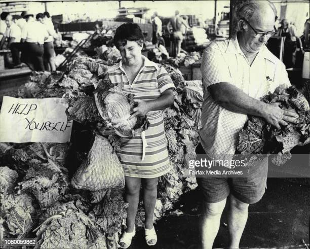 Mr Malcolm Cochrane and his wife of Cambridge Park help themselves from a pile of cabbages free for the taking at the city markets todayFlashback Mr...