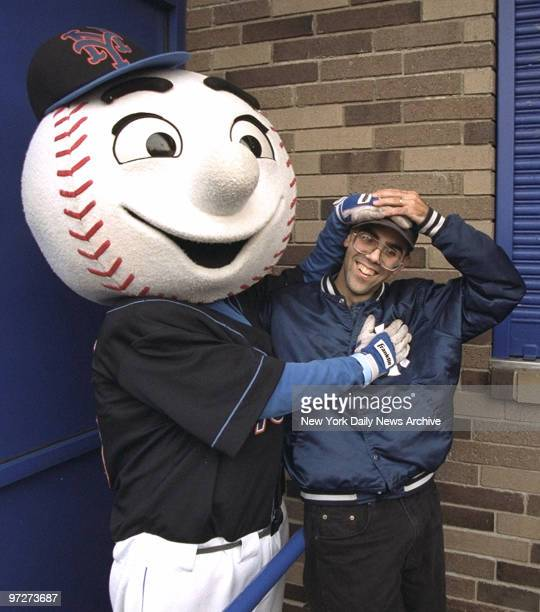 Mr Met tries to hide Yankee logos on Yankee fan Joe Garruba who was the first chosen to purchase Mets playoff tickets