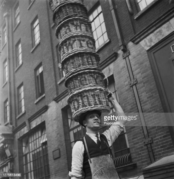 Mr Pyser a member of the Bow Street Company of Local Defence Volunteers or Home Guard carries a stack of wicker baskers on his head at work as a...