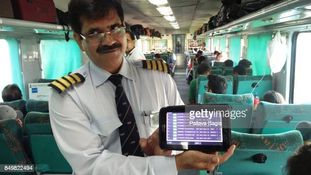 HARIDWAR UTTARAKHNAD INDIA SEPTEMBER 15 Mr Ramesh Kumar Assistant Superintendent on the Shatabadi Express a high speed train using a mobile tablet to...
