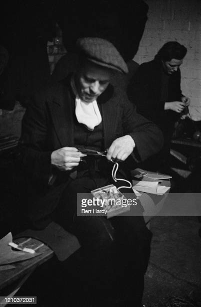 Mr Rendle cuts out the soles of a pair of slippers he is making in a craft lesson given by London County Council teachers at an air raid shelter in...