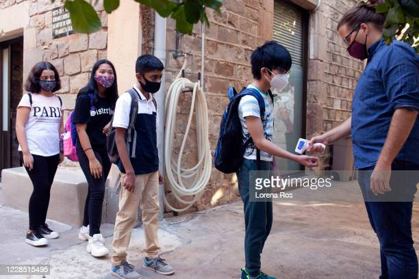 Mr. Ros, brother of the photographer, Teacher of Eso 1, takes the temperature of his students during the first day of school at Vedruna Angels School...