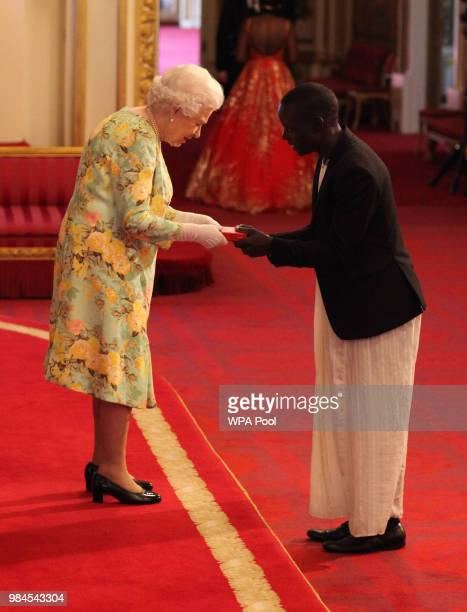 Mr Stephen Katende from Uganda receives his Young Leaders Award from Queen Elizabeth II during the Queen's Young Leaders Awards Ceremony at...