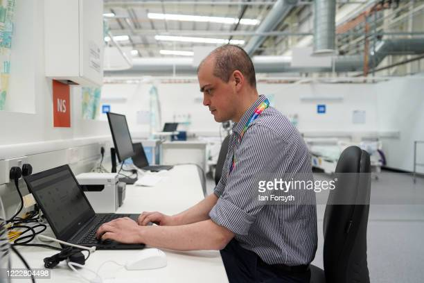 Mr Stephen Platts, a medical student, checks a computer at the nursing station in ward 6 at the new NHS Nightingale North East hospital opened in...