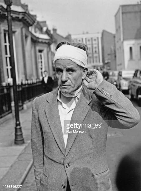 Mr T Harper, his head wrapped in a bandage after he was stabbed during the racially-motivated riots that took place in the Notting Hill area, arrives...